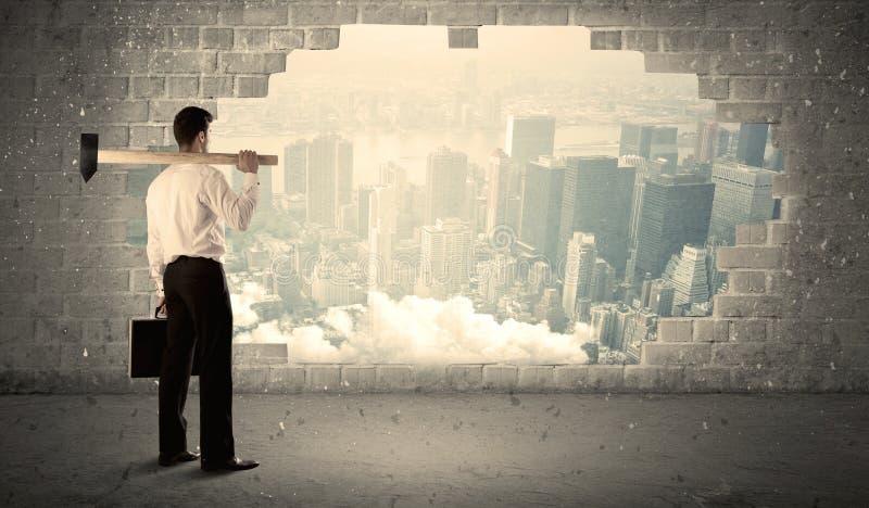 Hombre de negocios que golpea la pared con el martillo en la opinión de la ciudad fotografía de archivo