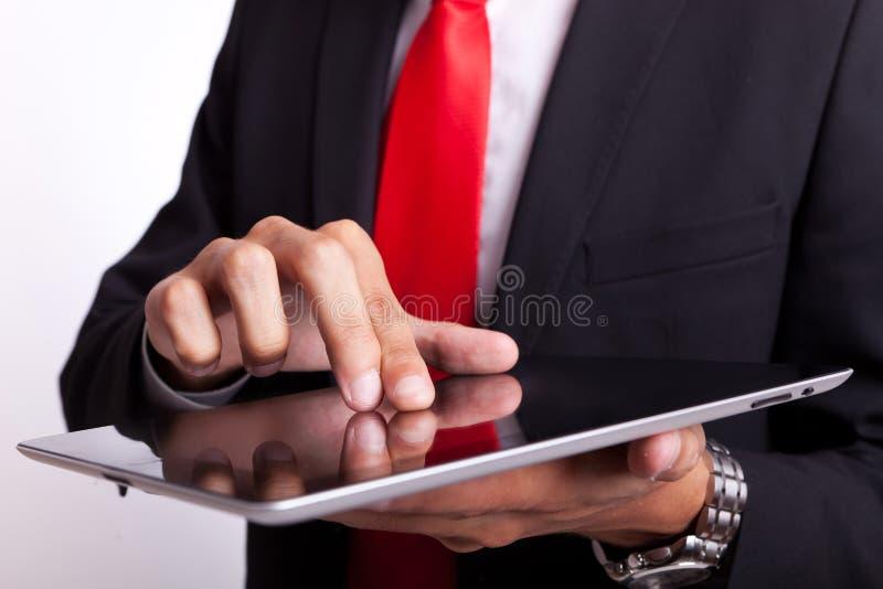 Hombre de negocios que golpea ligeramente y que hojea en la pista imagen de archivo libre de regalías