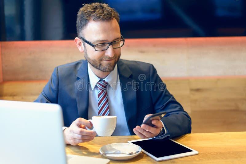 Hombre de negocios que goza del café y que comprueba un móvil imagen de archivo libre de regalías