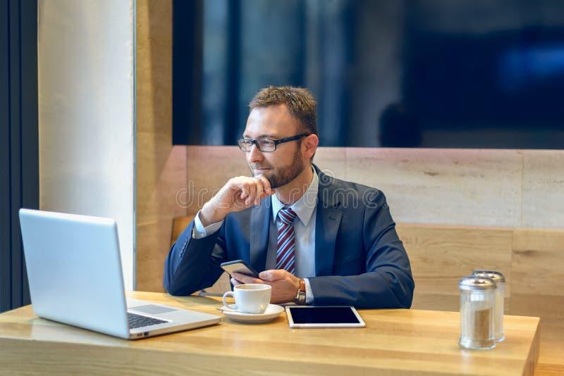Hombre de negocios que goza del café y que comprueba un móvil foto de archivo libre de regalías