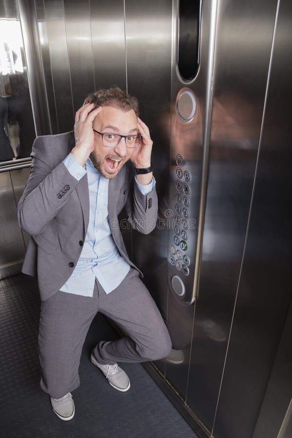 Hombre de negocios que grita en el elevador fotos de archivo
