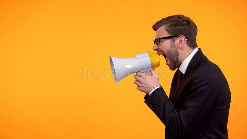 Hombre de negocios que grita en el meg?fono, aviso de las noticias de ?ltima hora, lugar para el texto fotografía de archivo