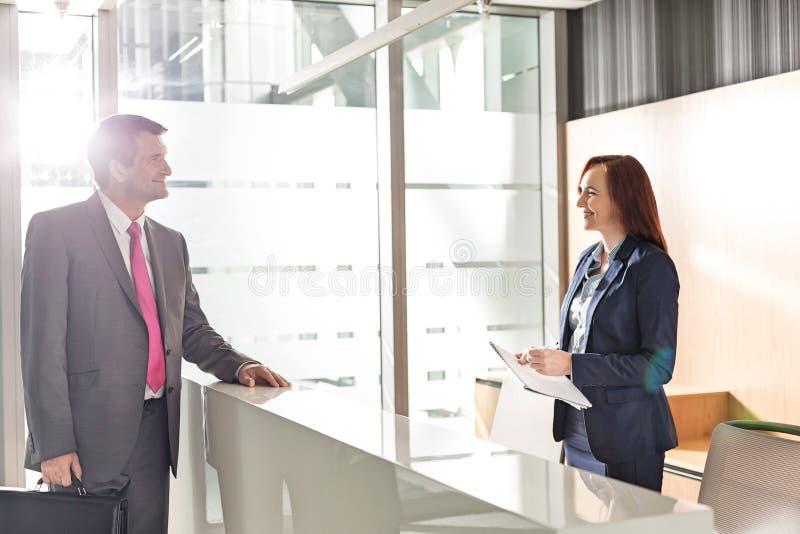Hombre de negocios que habla con el recepcionista en oficina fotos de archivo libres de regalías