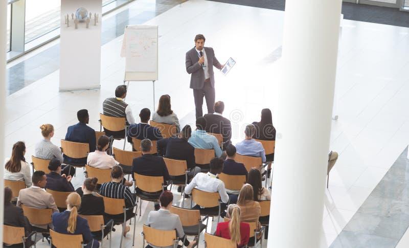 Hombre de negocios que habla delante de hombres de negocios mientras que sostiene la tableta y el micrófono digitales en el conf imagen de archivo libre de regalías