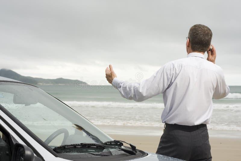 Hombre de negocios que habla en el teléfono celular al lado de su coche foto de archivo