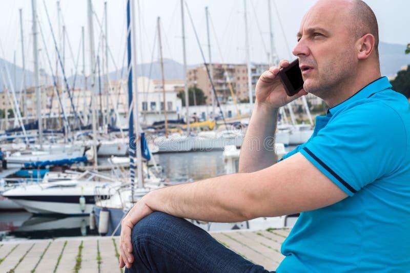 Hombre de negocios que habla en el teléfono cerca del puerto lujoso foto de archivo libre de regalías