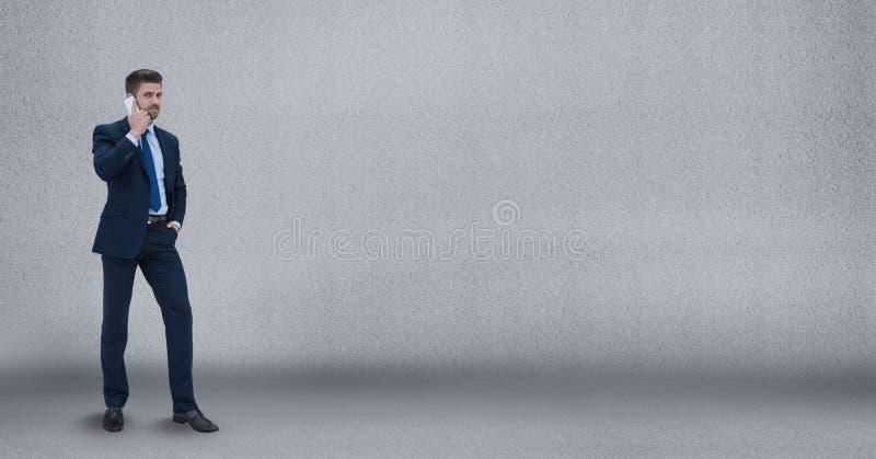 Hombre de negocios que habla en el teléfono contra fondo gris de la pared imagen de archivo