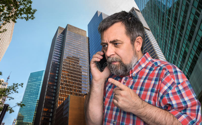 Hombre de negocios que habla en el teléfono móvil en la megalópoli imágenes de archivo libres de regalías