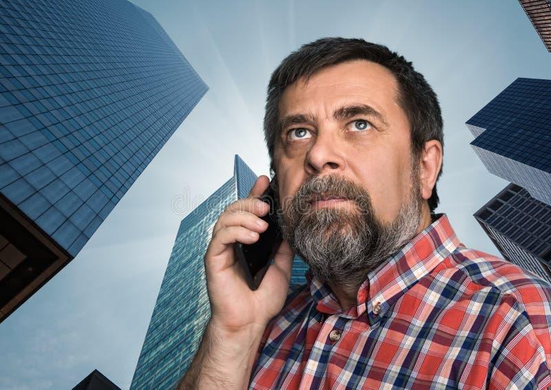 Hombre de negocios que habla en el teléfono móvil en la megalópoli imagen de archivo