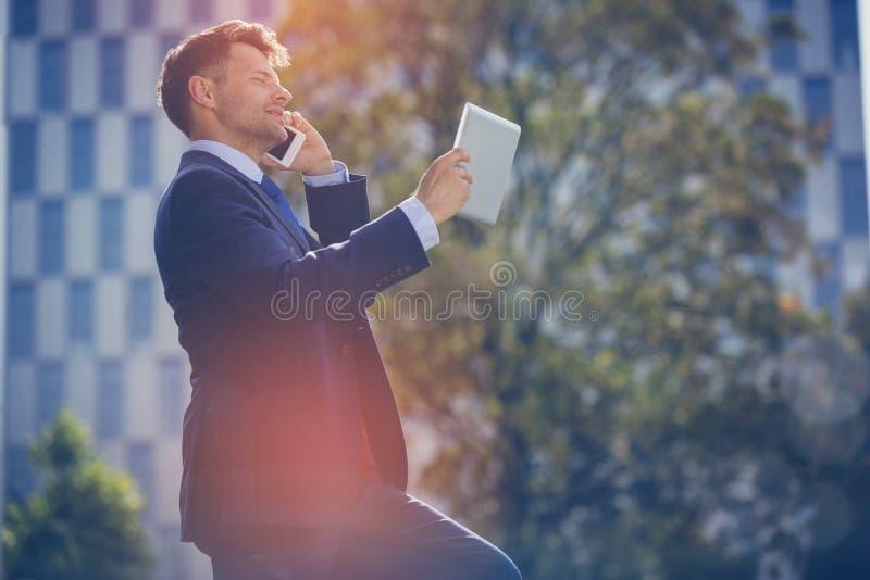 Hombre de negocios que habla en el teléfono móvil mientras que usa la tableta digital imágenes de archivo libres de regalías