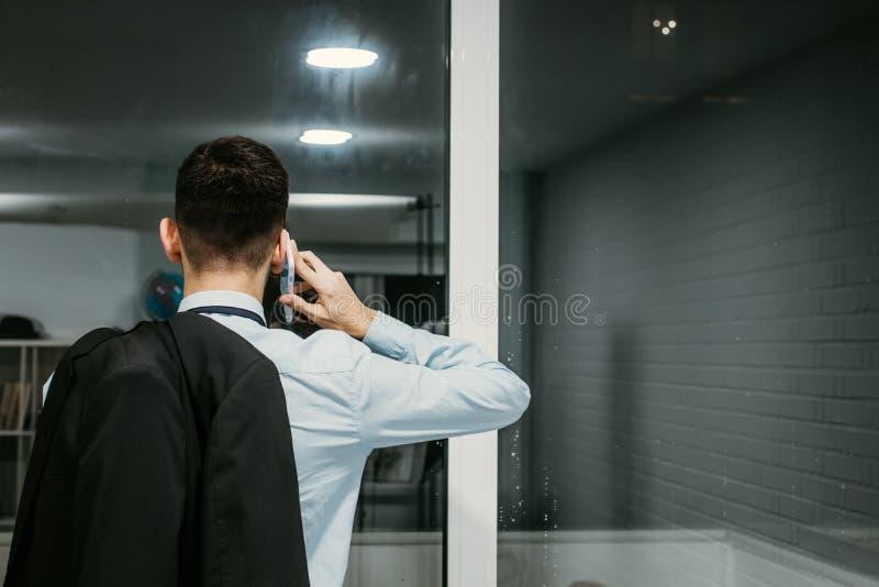 Hombre de negocios que habla en el tel?fono m?vil foto de archivo libre de regalías