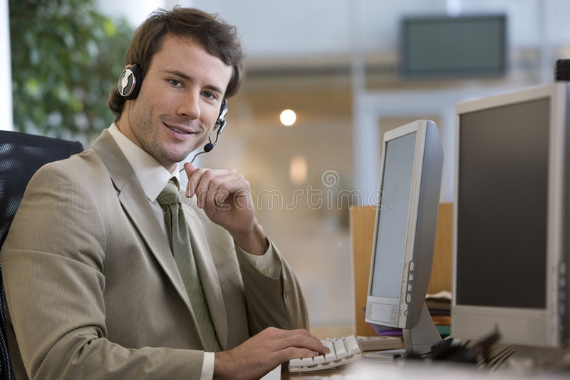 Hombre de negocios que habla en un receptor de cabeza imagen de archivo