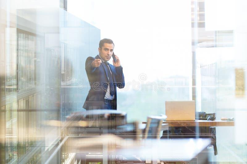 Hombre de negocios que habla en un teléfono móvil en la oficina corporativa, señalando a la cámara fotografía de archivo