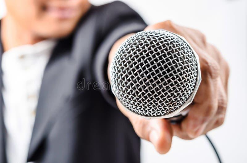 Hombre de negocios que hace discurso con gesticular del micrófono y de la mano imagen de archivo