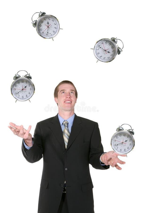 Hombre de negocios que hace juegos malabares su tiempo foto de archivo