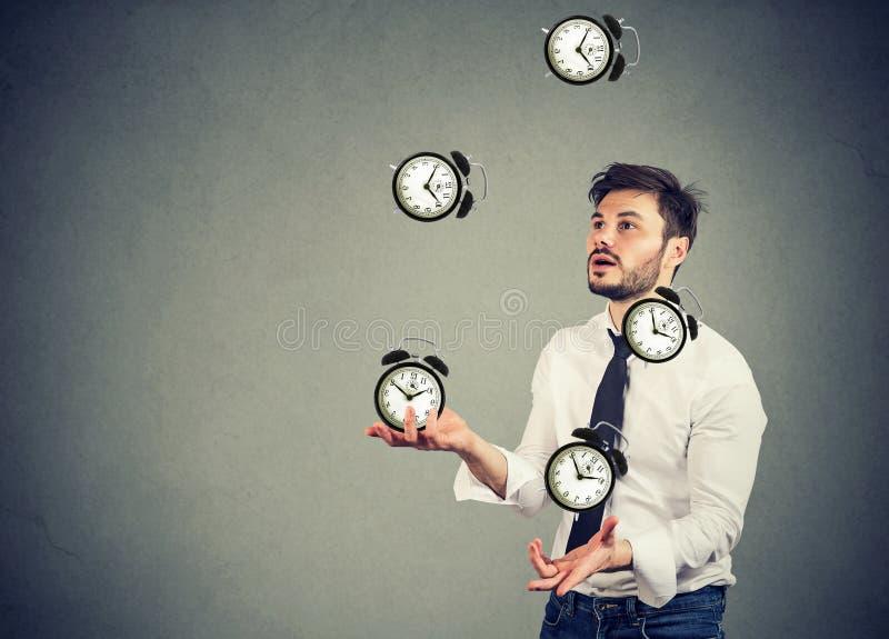 Hombre de negocios que hace juegos malabares sus despertadores del tiempo fotos de archivo