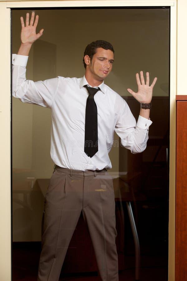 Hombre de negocios que hace la cara en la pared de cristal imagenes de archivo