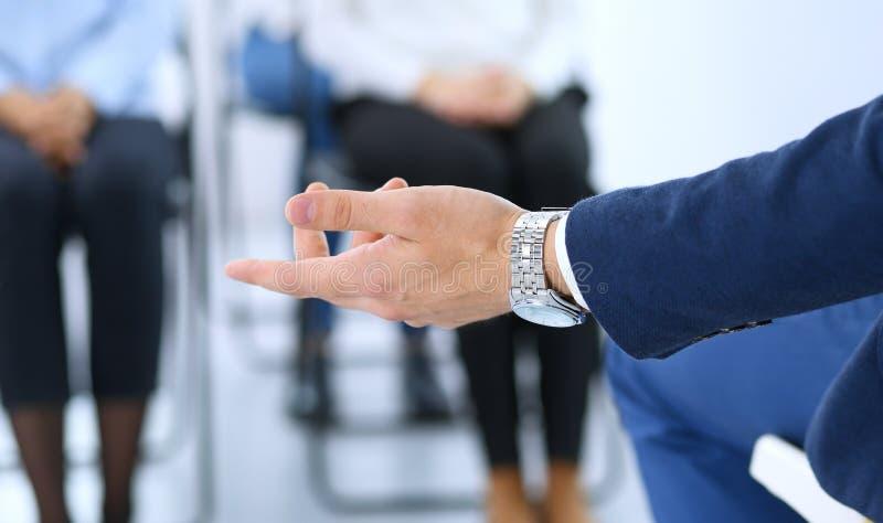 Hombre de negocios que hace la presentación al grupo de personas Presidente que entrega un seminario a sus colegas o entrenamient fotografía de archivo