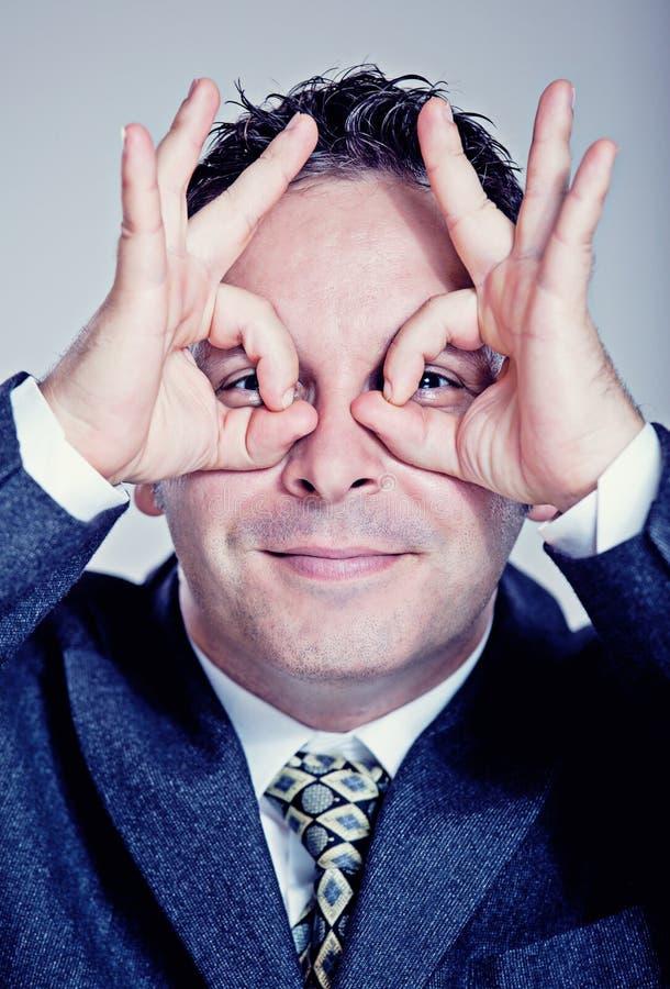 Hombre de negocios que hace los prismáticos con sus manos fotos de archivo