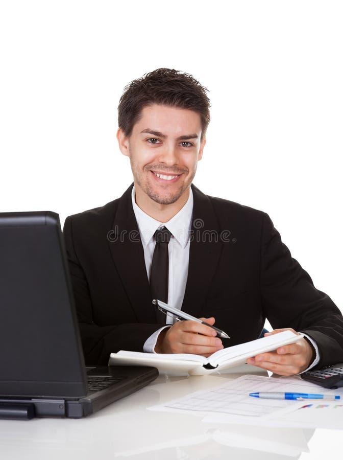Hombre de negocios que hace una nota en su diario imagen de archivo