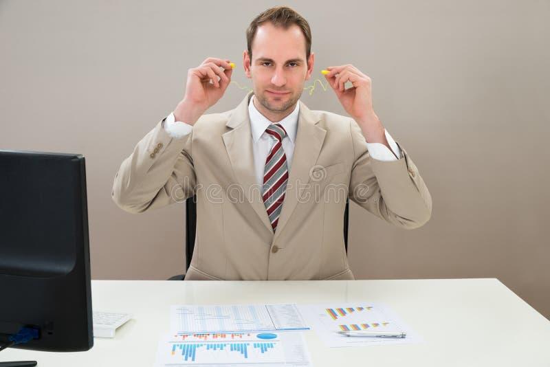 Hombre de negocios que inserta el auricular en oídos imagen de archivo libre de regalías