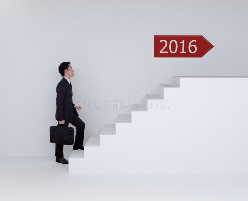 Hombre de negocios que intensifica en las escaleras a 2016 fotografía de archivo