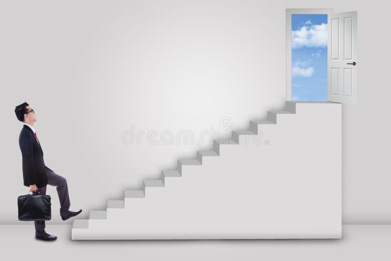 Hombre de negocios que intensifica la escalera a la puerta del éxito fotografía de archivo libre de regalías