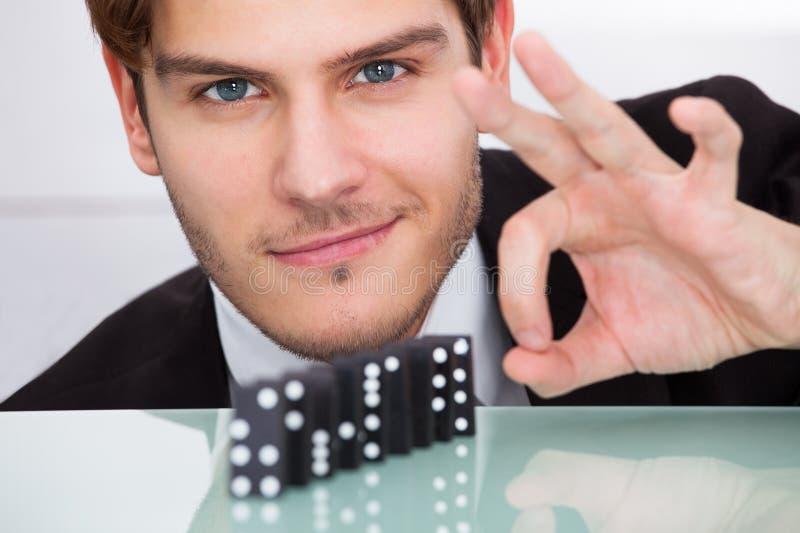 Hombre de negocios que juega dominó imagen de archivo libre de regalías