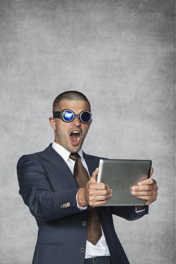 Hombre de negocios que juega a juegos en su tableta imagen de archivo