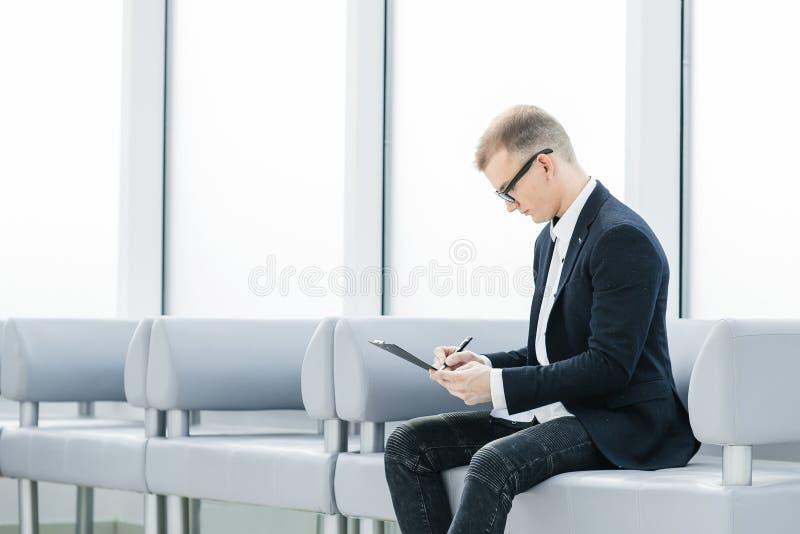 Hombre de negocios que lee un documento de negocio que se sienta en el pasillo de la oficina imagenes de archivo