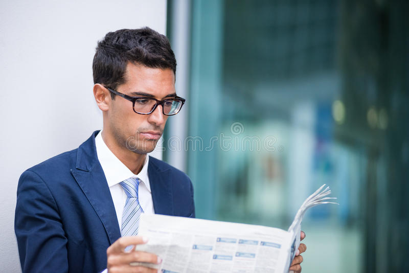 Hombre de negocios que lee un periódico imagen de archivo