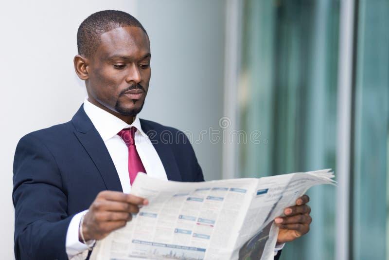 Hombre de negocios que lee un periódico imagen de archivo libre de regalías