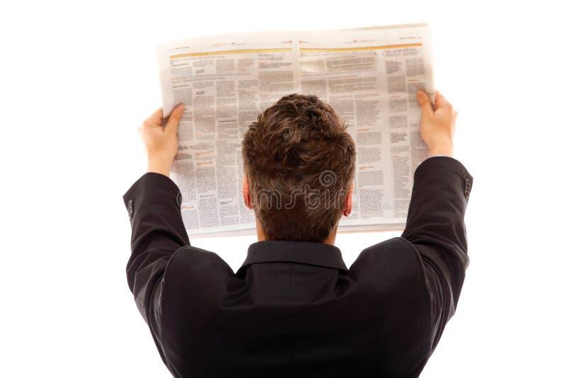 Hombre de negocios que lee un periódico aislado imagen de archivo