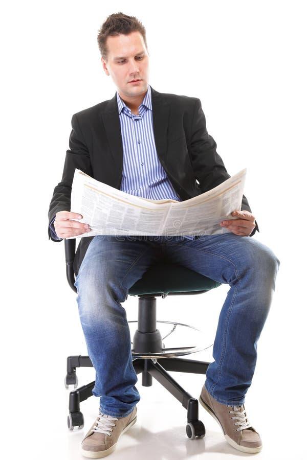 Hombre de negocios que lee un periódico aislado foto de archivo