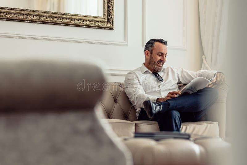 Hombre de negocios que lee una revista en la habitación foto de archivo