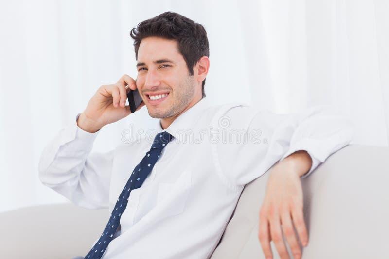 Hombre de negocios que llama con su teléfono móvil en el sofá imagen de archivo
