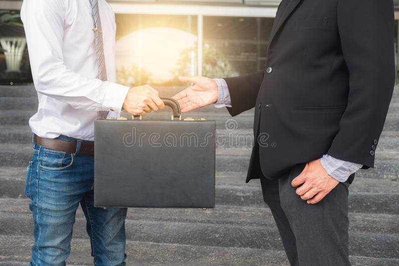 Hombre de negocios que llena la cartera negra para intercambiar trato de la transferencia imagen de archivo