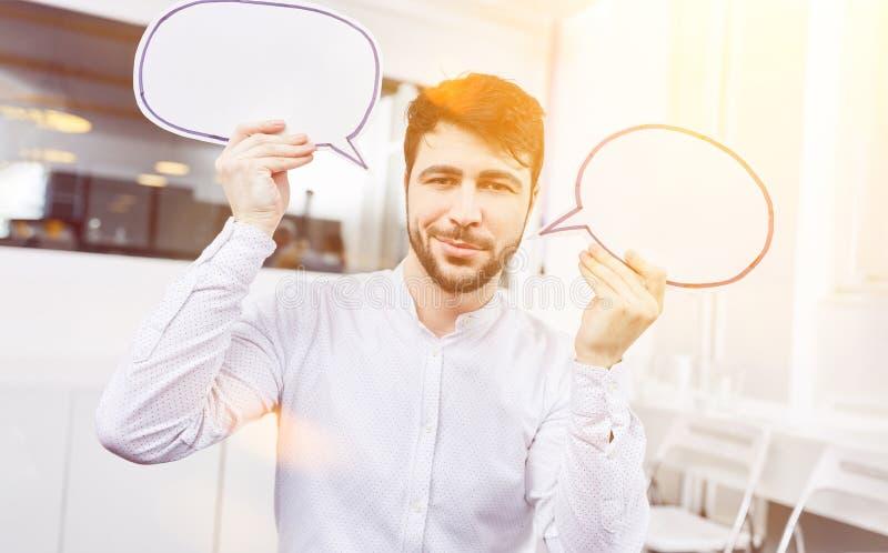 Hombre de negocios que lleva a cabo burbujas del discurso imagen de archivo