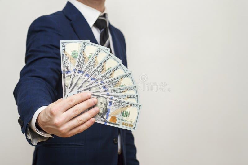 Hombre de negocios que lleva a cabo dólares del efectivo del dinero en manos de pasarlas al cliente Hombre de negocios que da el  fotos de archivo
