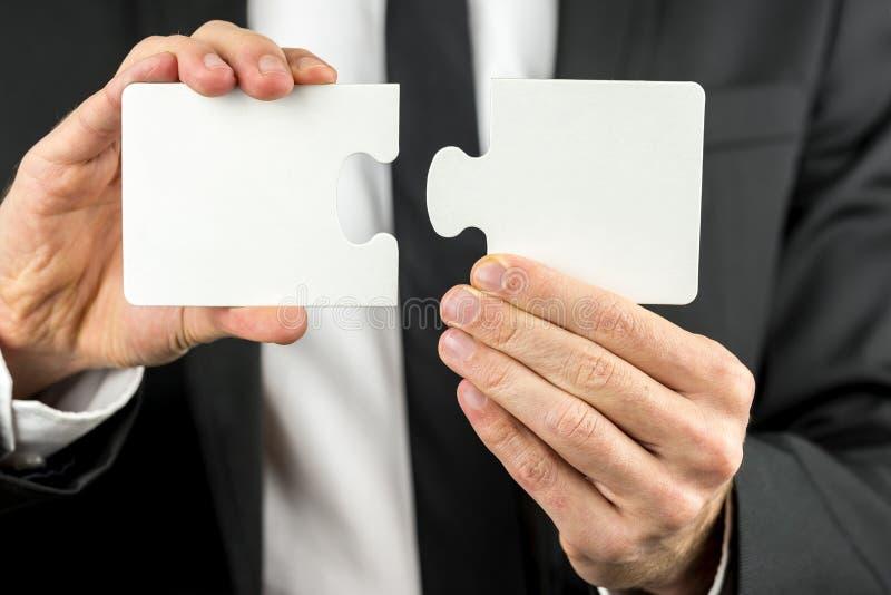 Hombre de negocios que lleva a cabo dos pedazos de un rompecabezas en blanco fotografía de archivo libre de regalías