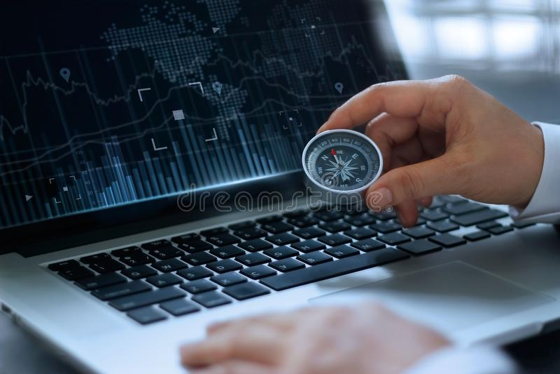 Hombre de negocios que lleva a cabo el compás con la búsqueda del ordenador portátil de la pantalla foto de archivo
