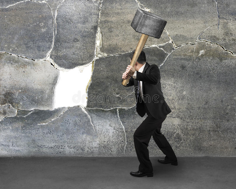 Hombre de negocios que lleva a cabo el sedgehammer para agrietar la pared foto de archivo libre de regalías