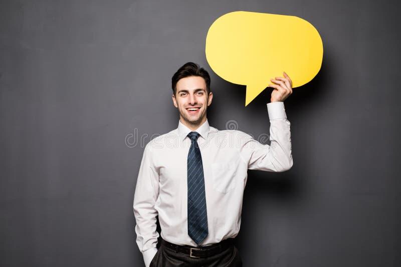 Hombre de negocios que lleva a cabo la burbuja del discurso en fondo gris fotos de archivo