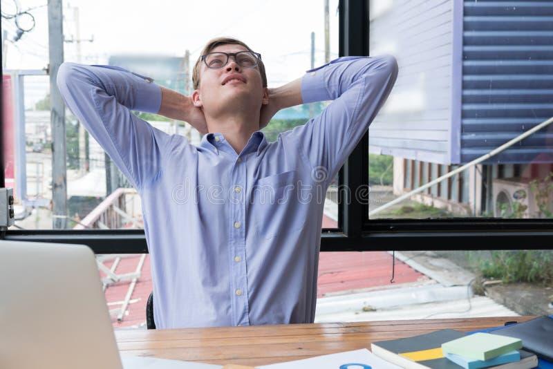 Hombre de negocios que lleva a cabo la cabeza del behide de las manos que se relaja en silla en offic foto de archivo