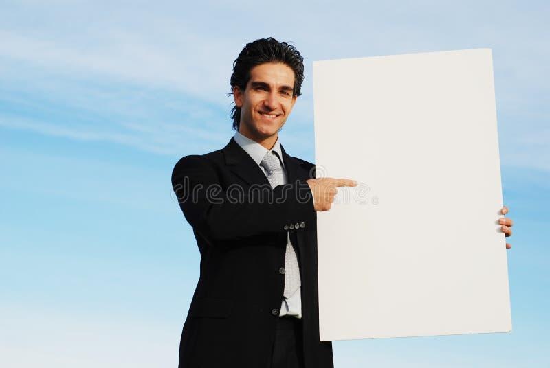 Hombre de negocios que lleva a cabo a la tarjeta en blanco fotografía de archivo
