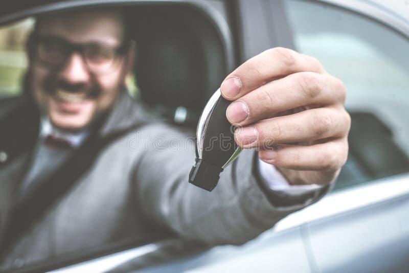 Hombre de negocios que lleva a cabo llave del coche imágenes de archivo libres de regalías