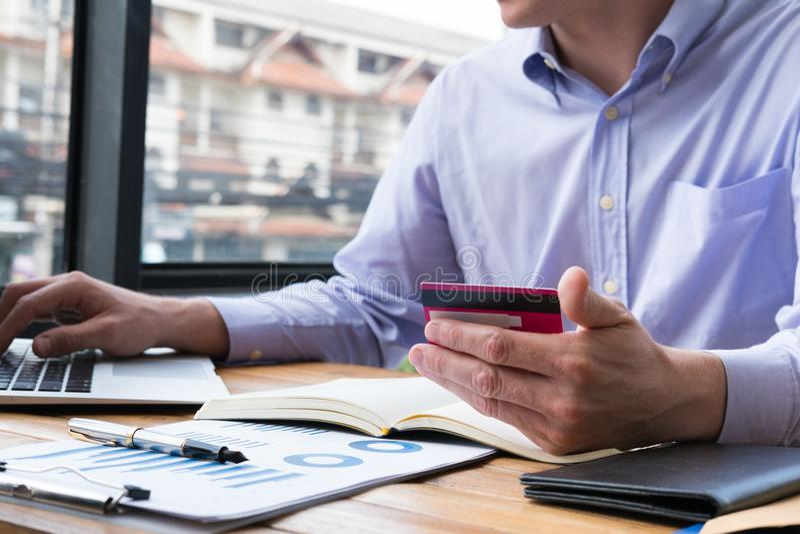 Hombre de negocios que lleva a cabo números que mecanografían de la tarjeta de crédito en keybo del ordenador fotografía de archivo