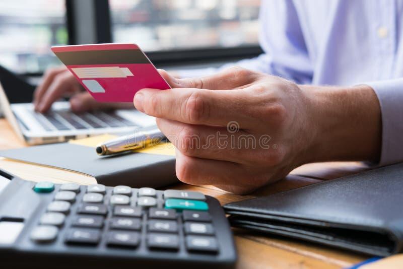 Hombre de negocios que lleva a cabo números que mecanografían de la tarjeta de crédito en keybo del ordenador imagen de archivo libre de regalías