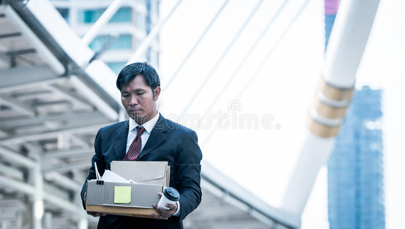 Hombre de negocios que lleva a cabo sostener la caja de cartón con los objetos personales que salen de trabajo encendido foto de archivo libre de regalías