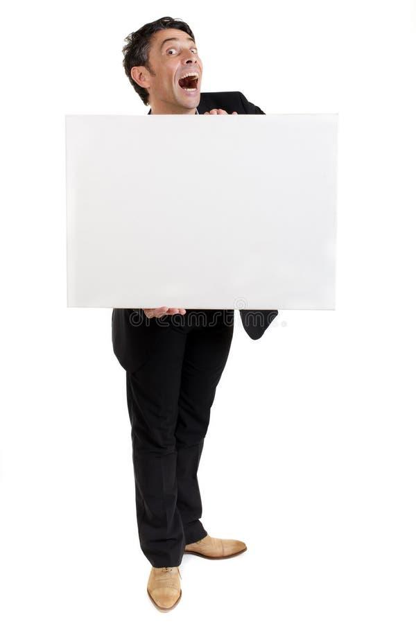 Hombre de negocios que lleva a cabo un blanco en blanco foto de archivo